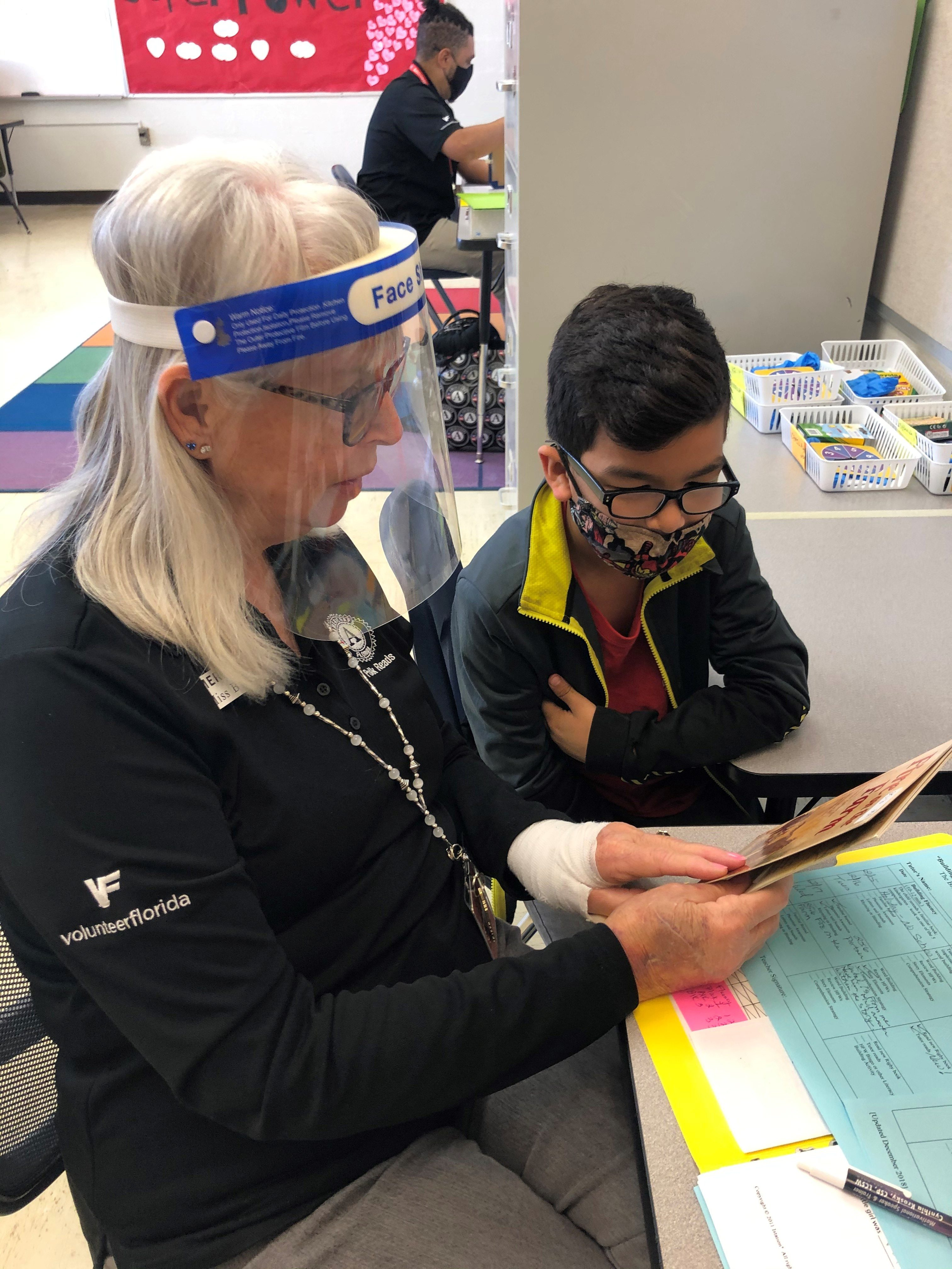 AmeriCorps member reading a book to a student