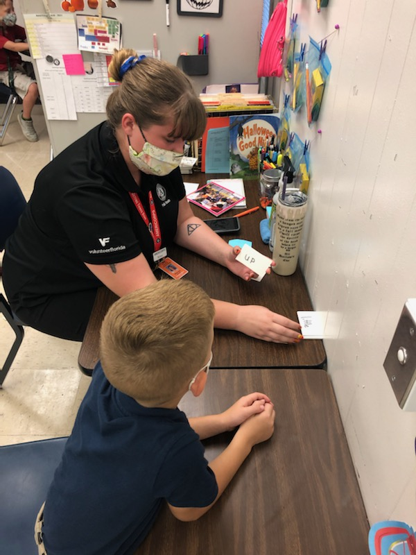 AmeriCorps member tutoring a student with flashcards