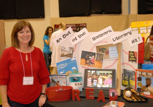 Woman posing next to her Ballpark Literary info board