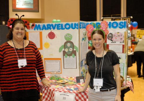 2 Woman posing next to their info board about bugs and nature
