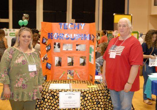 2 Women posing next to their Techy Regrouping info board