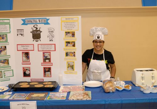 Woman posing next to her Cooking with Steam display board