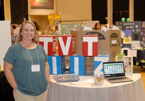 Woman posing next to her TVT IIZ display