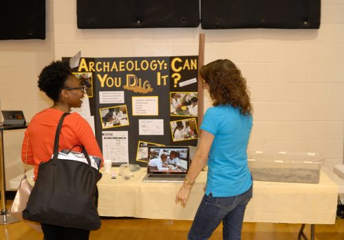 Woman describing her Archaeology info board to a visitor