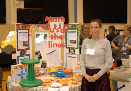 Woman posing with her Math Outside the Lines info board