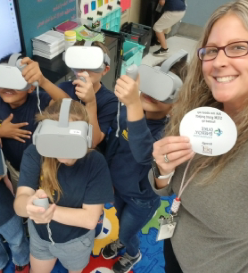 Teacher posing for a picture with kids wearing virtual reality headsets