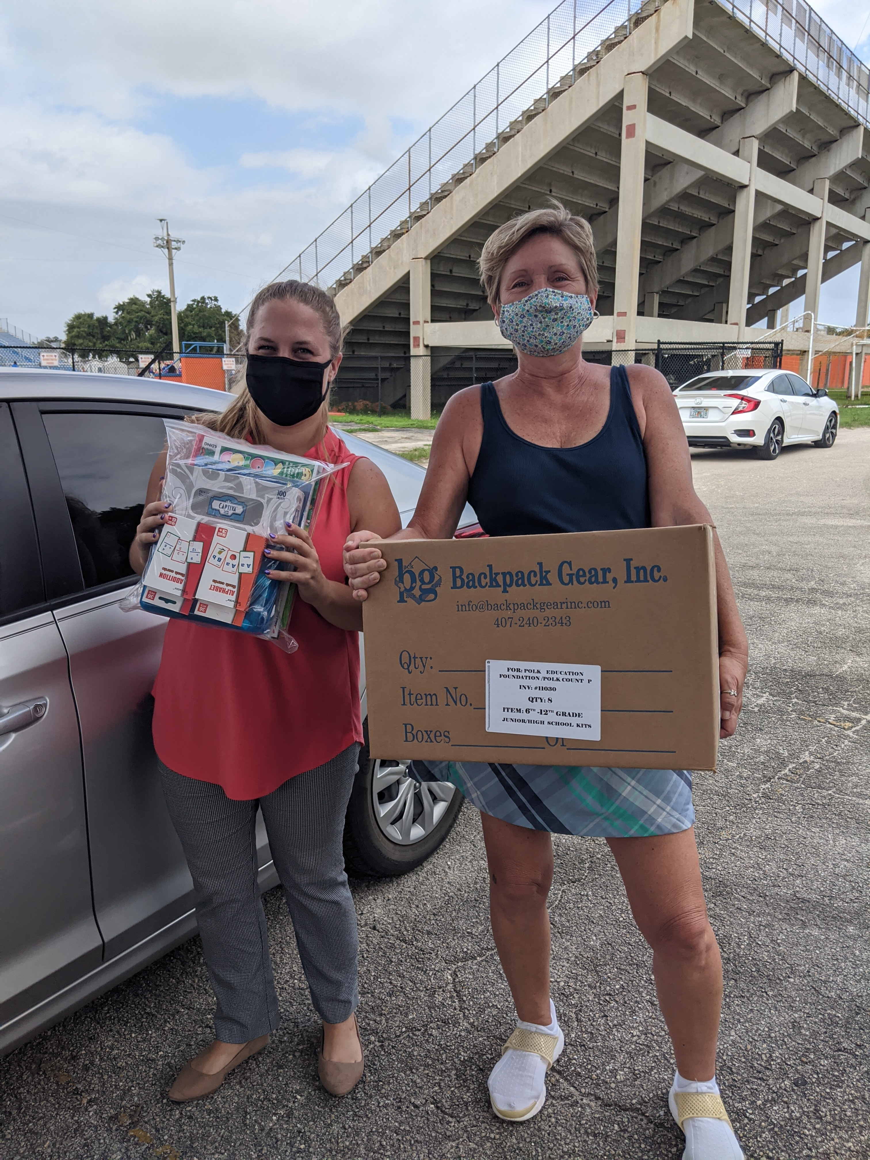 2 Women posing for a picture holding supplies