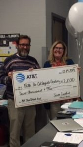 Under ATT STEM at Work Grant Polk Pre-collegiate Academy, photograph of two people holding a check for 2,000 dollars