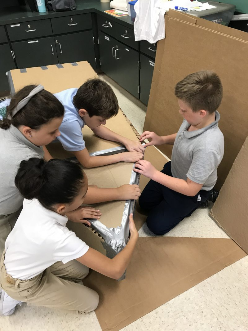 Combee Academy students working on a cardboard boat.
