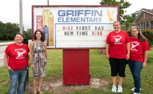 Jennie Cyran posing in front of the sign at Griffin Elementary.