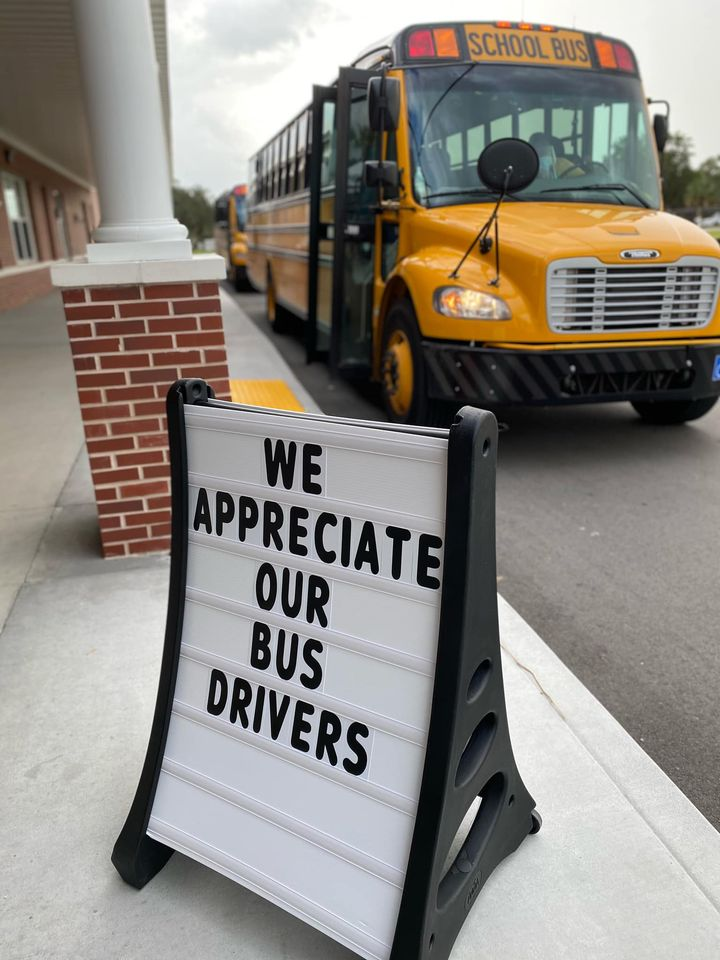 """Photo of a bus next to a sign that says """"We appreciate our bus drivers."""""""