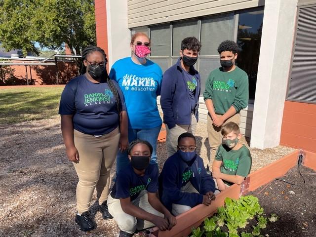 Teacher Tara Boucher gardening with students