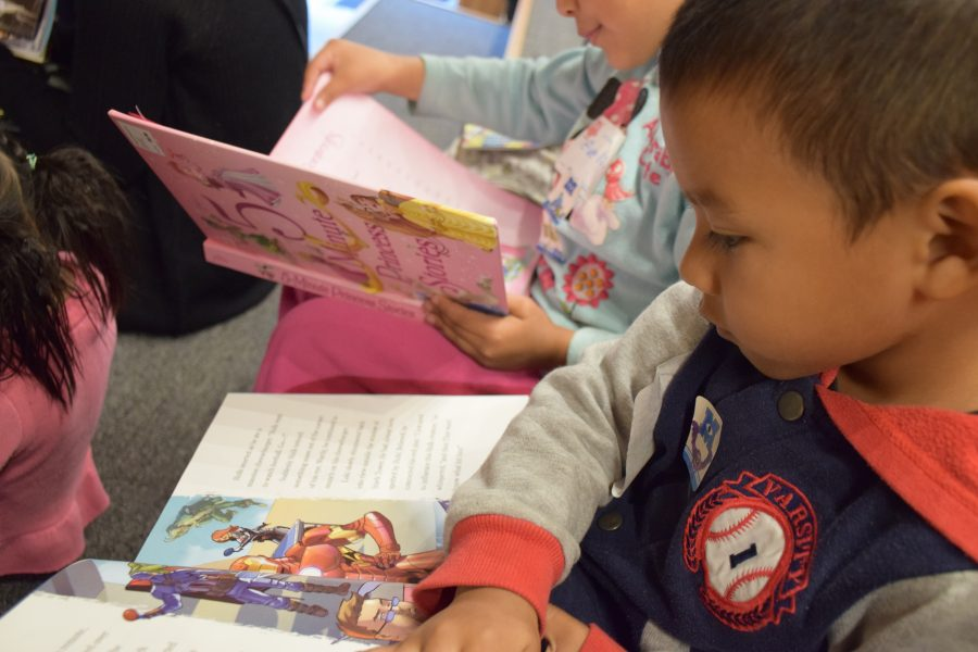 Young children reading during a PCPC early literacy event at Garner Elementary.