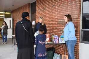 Families exploring new books during the early literacy event at Garner Elementary