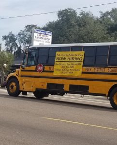 Photo of a PCPS school bus with an employment info banner.