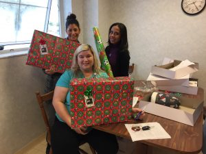 PCPS social workers gift-wrap boxes full of donated toys and items for students in need.