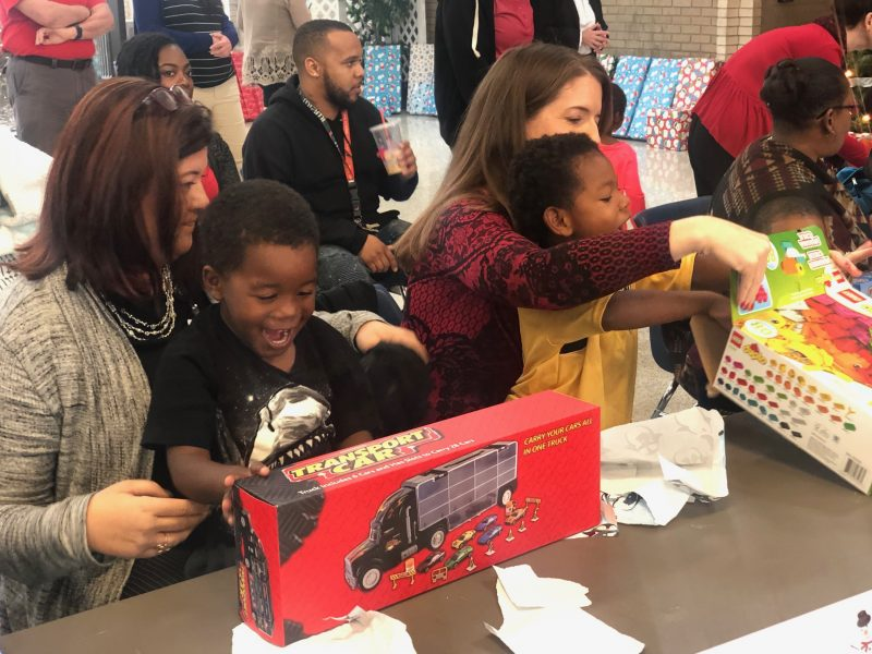 Preschool students enjoy donated gifts at the Kiddie Christmas event.