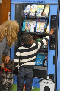Young student using the bookworm vending machine at Kingsford Elementary