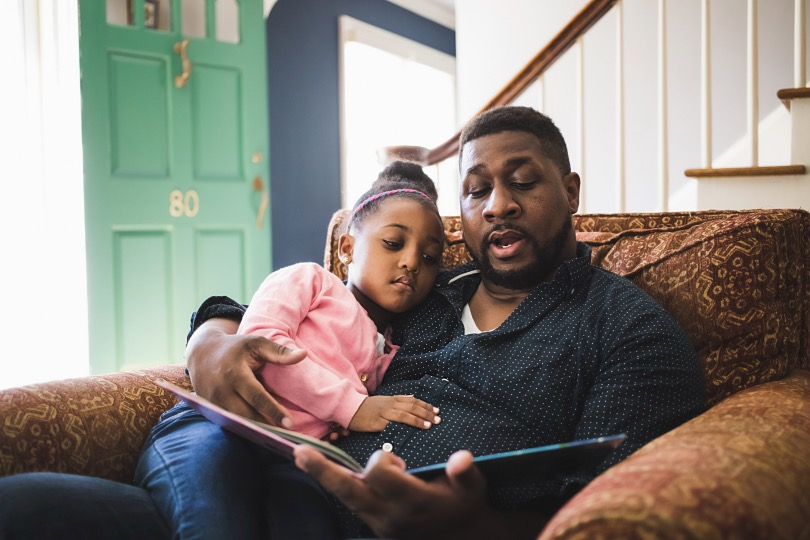 Young female kid sitting on fathers lap reading a book