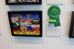 Jaqueline Navarro's artwork displayed with a green ribbon