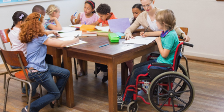 Young female student sitting in a wheelchair at a table with other students while working with a teacher