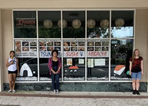 Students painting holiday scenes on downtown Lakeland storefronts.