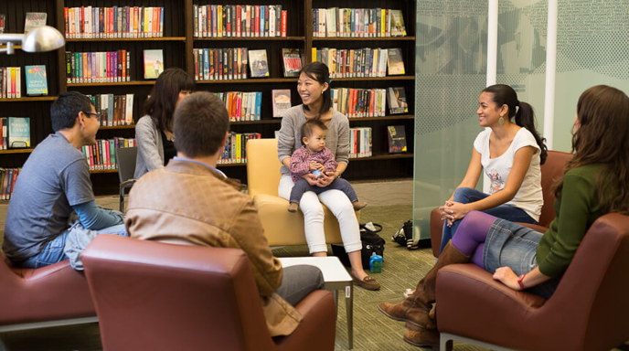 Families sitting in a library talking