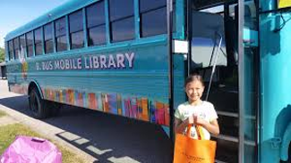 Young girl holding an orange bag standing in front of the Mobile Library Bus
