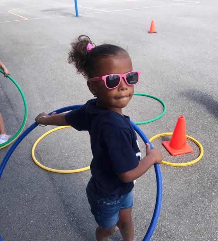 A little girl playing hula hoop
