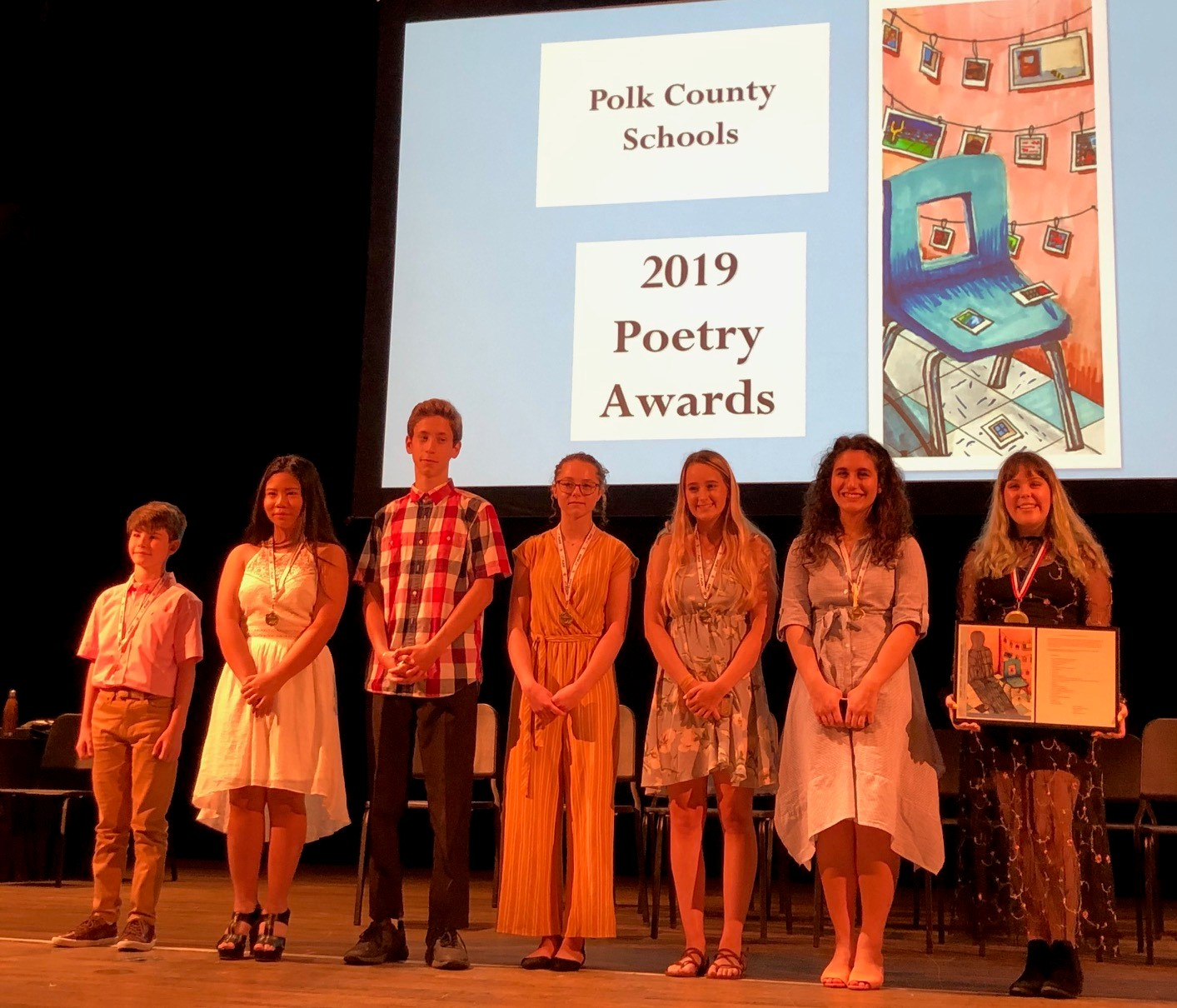 Poetry 1st Place Winners standing on stage wearing medals