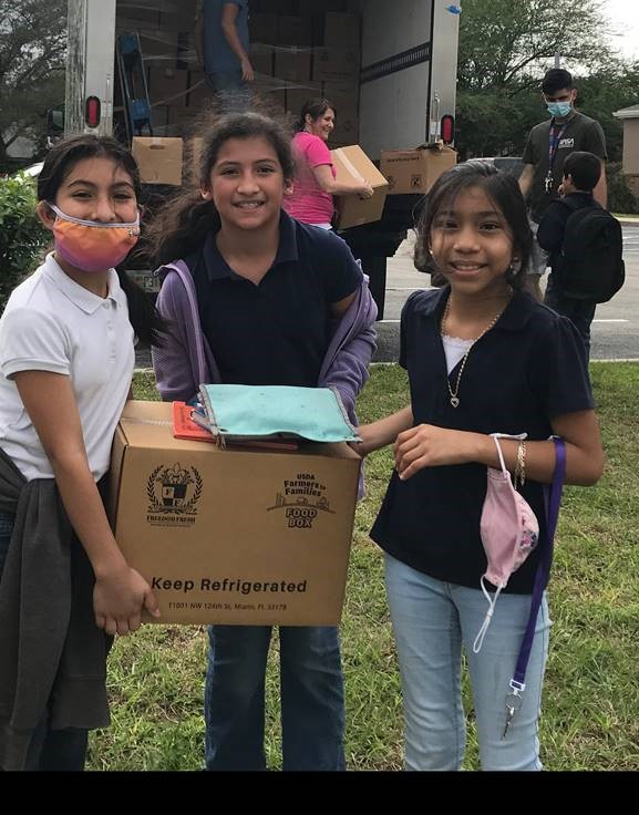 Photo of three girls receiving food from a mobile food pantry