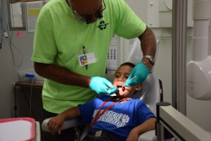 A child receives free dental care during the Give Kids A Smile event at Traviss Technical College.