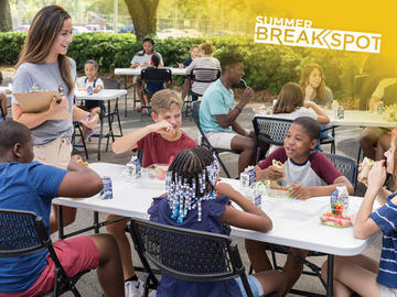 Students sitting at a table eating a snack.