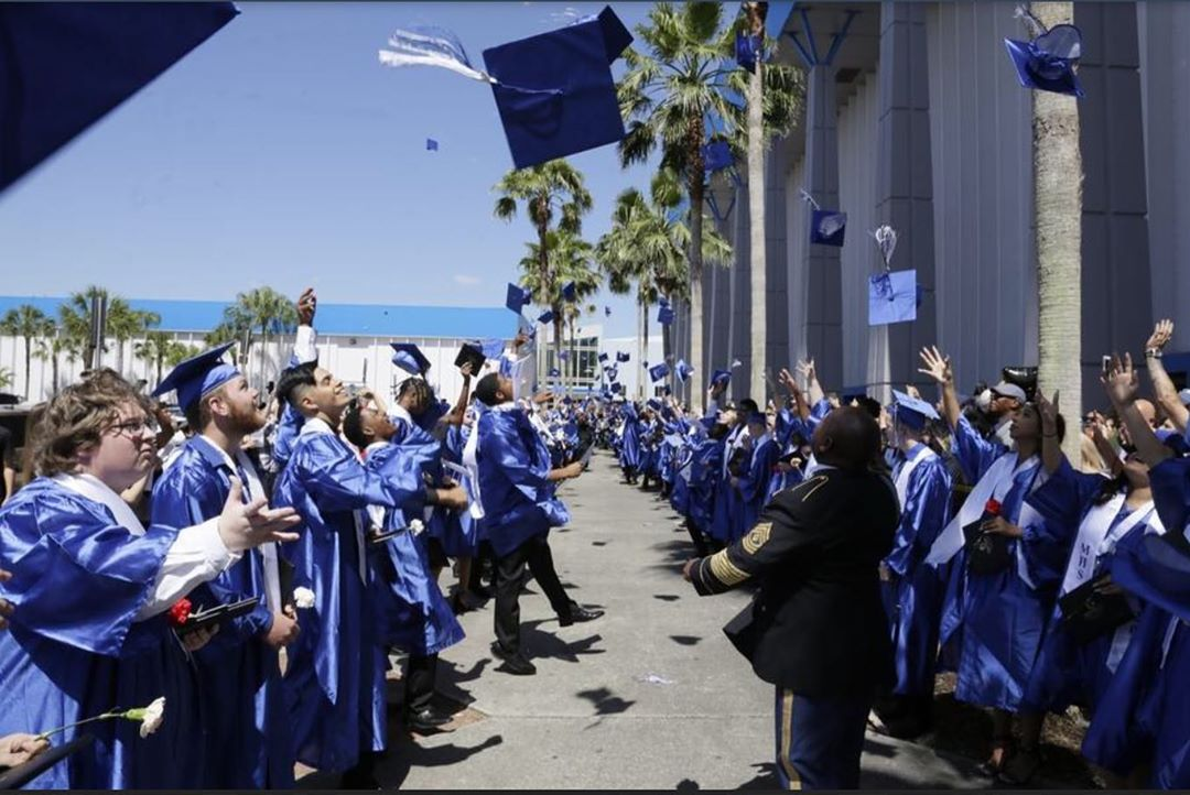 Students outside throwing their caps in the air celebrating their graduation