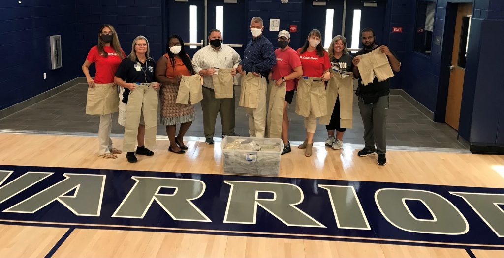 State Farm employees and Westwood Middle staff posing with donated khakis